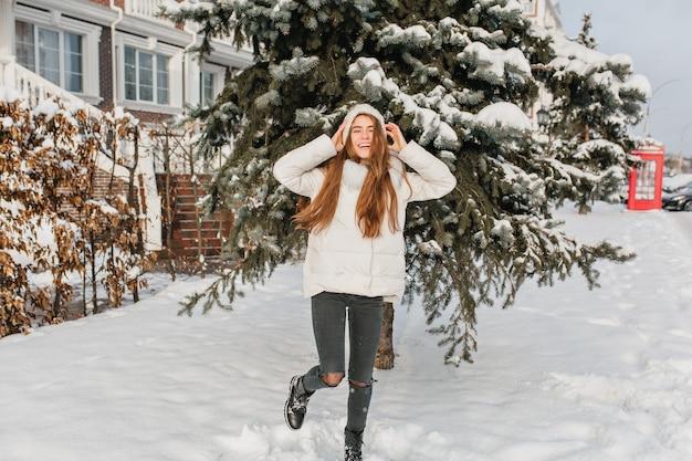 Portret van gemiddelde lengte van ontspannen blonde vrouw in zwarte broek dansen op besneeuwde straat met glimlach. buiten foto van grappige sierlijke vrouw poseren met handen omhoog voor groene sparren in winterdag.