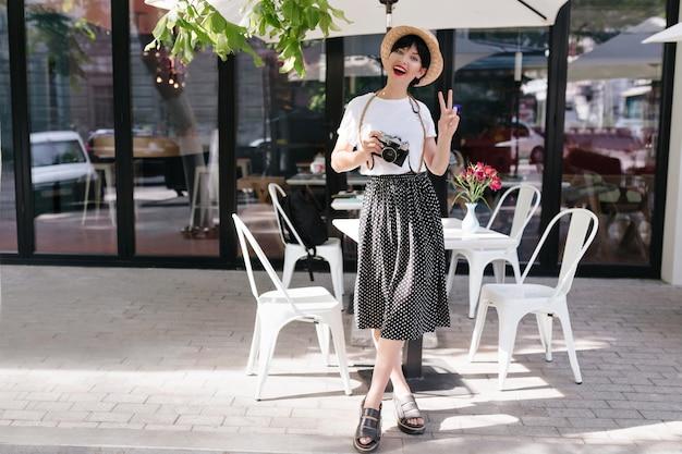 Portret van gemiddelde lengte van opgewonden donkerbruine jonge vrouw in zwarte rok en strohoed die zich met gekruiste benen en vredesteken bevinden