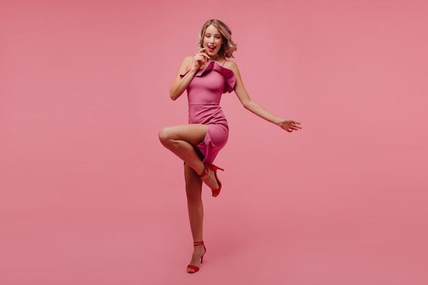 Portret van gemiddelde lengte van opgewonden krullende vrouw die zich op één been op roze muur bevindt