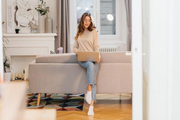 Portret van gemiddelde lengte van prachtige vrouwelijke freelancer in spijkerbroek die haar werk doet, met behulp van laptop
