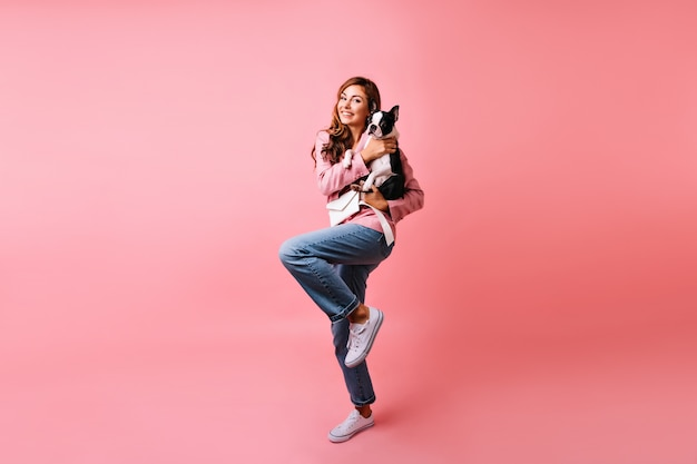 Portret van gemiddelde lengte van schattig meisje in trendy jeans met franse bulldog. dromerige blanke vrouw poseren met haar hond op roze.