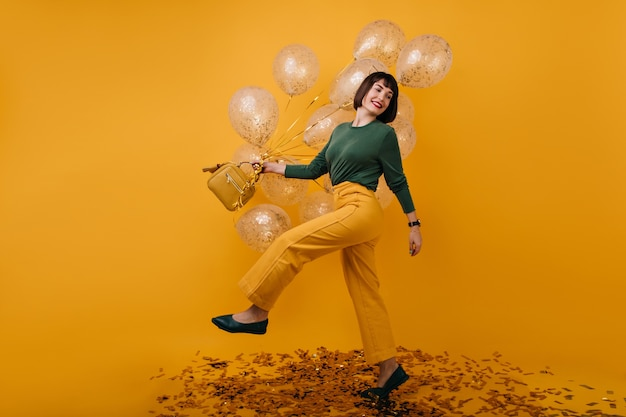 Portret van gemiddelde lengte van schattige vrouw dansen met feestballonnen. binnen schot van zalig donkerbruin meisje in gele broek met plezier op haar verjaardag.