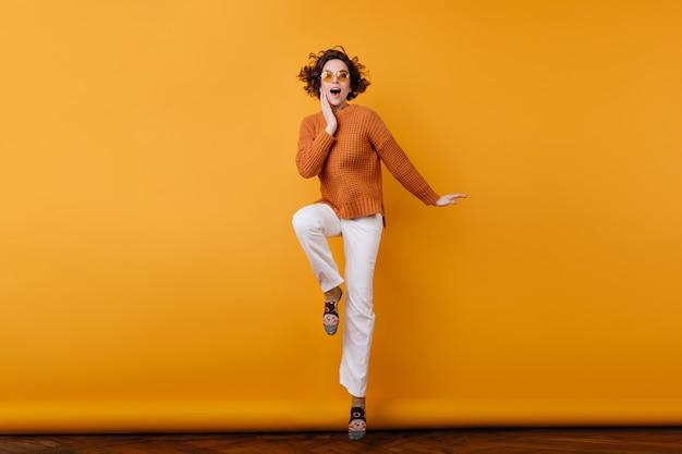 Portret van gemiddelde lengte van slanke krullende vrouw in vrijetijdskleding die op één been stellen