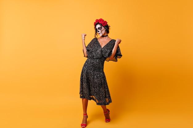Portret van gemiddelde lengte van slanke vrouw met rozen in haar die de dag van de doden vieren. schitterend meisje in mexicaanse feestuitrusting die op gele achtergrond danst.