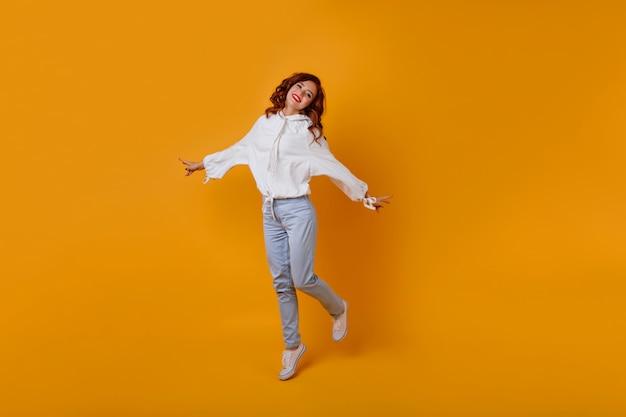 Portret van gemiddelde lengte van verbazend slank meisje met gemberhaar. kaukasische romantische vrouw die op gele muur danst.