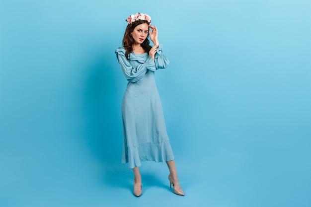 Portret van gemiddelde lengte van verfijnde dame in midi-jurk. vrouw met kroon van bloemen op blauwe muur.