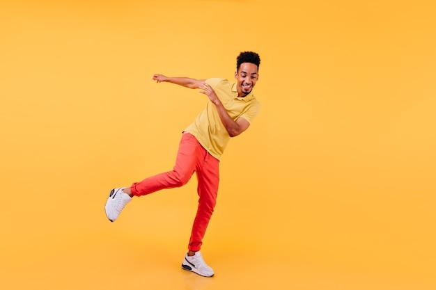 Portret van gemiddelde lengte van vrolijk afrikaans mannelijk model dat in gele schoenen danst. vrolijke zwarte man genieten.