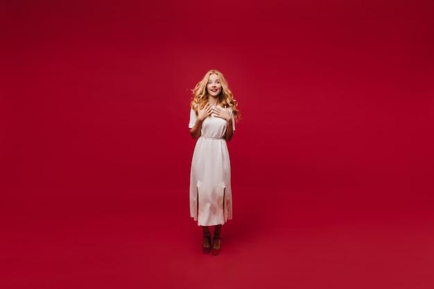 Portret van gemiddelde lengte van vrolijke vrouw in witte kleding. charmant langharige meisje geïsoleerd op rode muur.