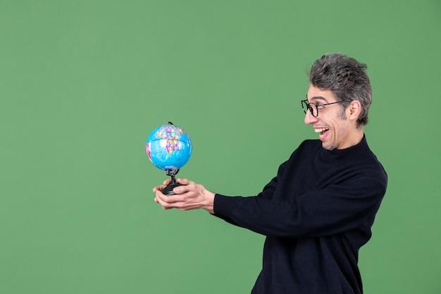 Portret van geniale man die aardebol aan iemand geeft groene achtergrond lucht natuur zee leraar ruimte school planeet