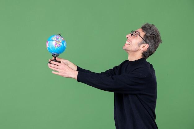 Portret van geniale man die aardebol aan iemand geeft groene achtergrond lucht natuur zee leraar school planeet