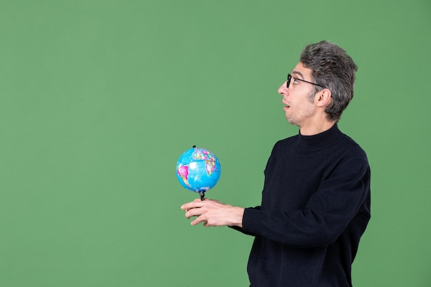 Portret van geniale man die aardebol aan iemand geeft groene achtergrond lucht zee leraar ruimte school planeet
