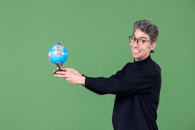 Portret van geniale man die aardebol aan iemand geeft groene achtergrond natuur zee leraar ruimte school planeet