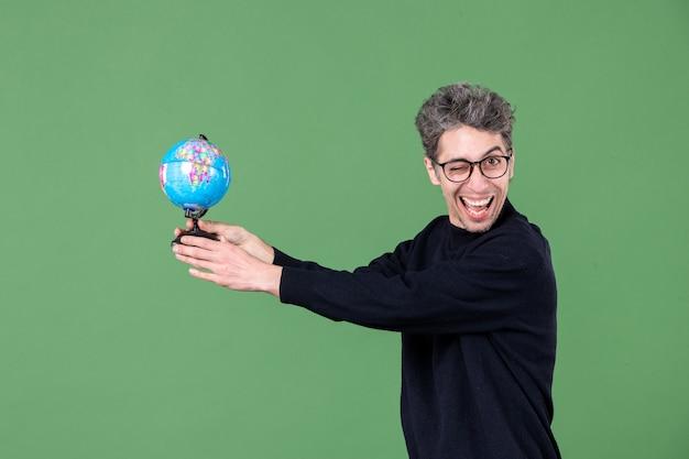 Portret van geniale man die een aardbol geeft aan iemand groene achtergrond lucht natuur zee leraar ruimte school planeten