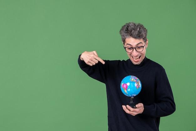 Portret van genie man met aarde wereldbol groene achtergrond lucht leraar school planeet natuur zee