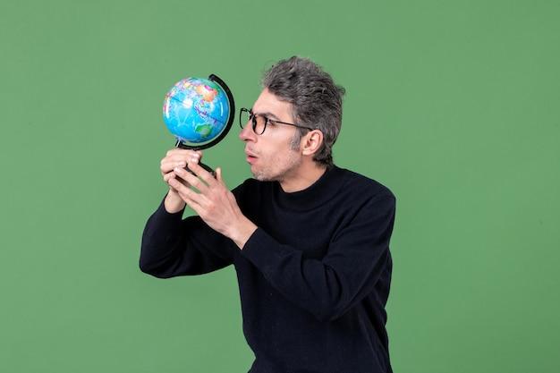 Portret van genie man verkennen aarde wereldbol studio opname groene achtergrond lucht zee planeet ruimte natuur leraar