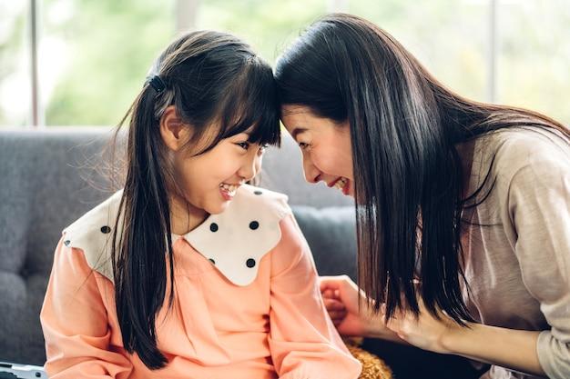Portret van geniet van de gelukkige moeder van de liefde aziatische familie en het kleine aziatische meisjeskind die en pret glimlachen hebben
