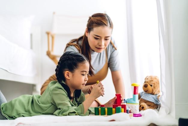 Portret van genieten van gelukkige liefde aziatische familie moeder en weinig aziatisch meisje glimlachend spelen met speelgoed bouwen houten blokken bordspel in momenten goede tijd thuis