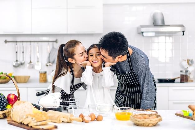 Portret van genieten van gelukkige liefde aziatische familie vader en moeder met aziatische meisje dochter kind plezier koken samen met koekjes bakken en cake ingrediënten op tafel in de keuken
