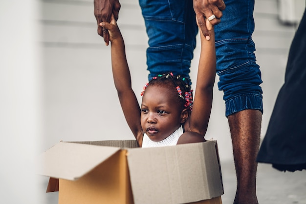 Portret van genieten van gelukkige liefde zwarte familie afro-amerikaanse vader en klein afrikaans meisje, zittend in een kartonnen doos