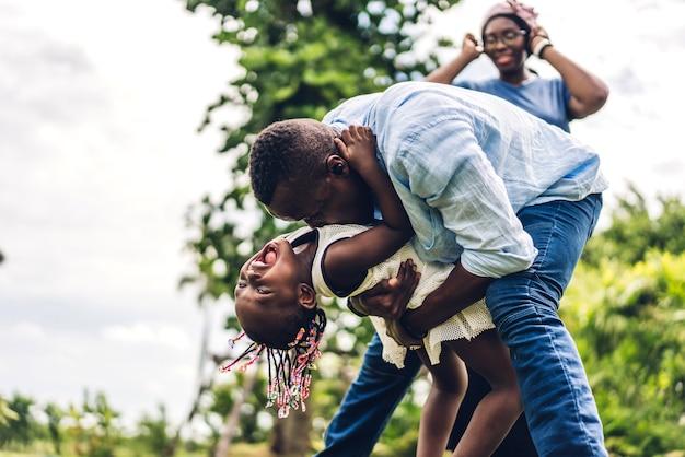 Portret van genieten van gelukkige liefde zwarte familie afro-amerikaanse vader en moeder met klein afrikaans meisje kind glimlachend en plezier momenten goede tijd