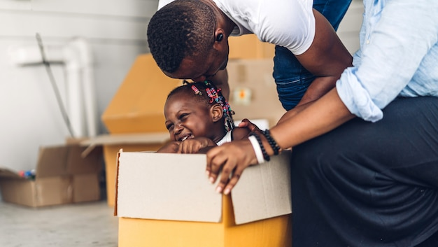 Portret van genieten van gelukkige liefde zwarte familie afro-amerikaanse vader en moeder met weinig afrikaans meisje glimlachend zitten in kartonnen doos