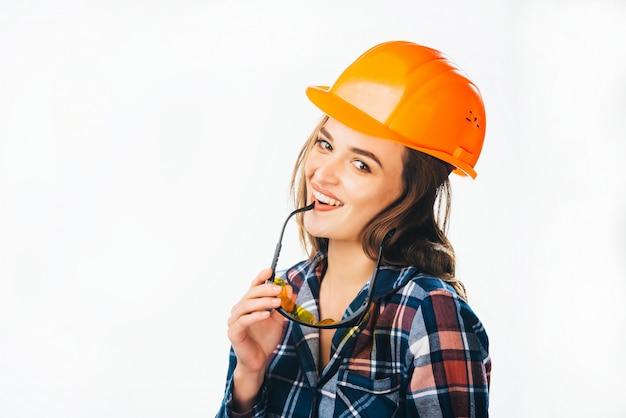 Portret van gepassioneerde vrouwelijke bouwer met helm en bril aan te raken haar lippen