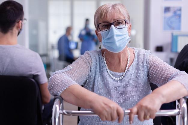 Portret van gepensioneerde gehandicapte patiënt in ziekenhuiskantoor kijkend naar camera met gezichtsmasker zittend op stoel in wachtkamerkliniek terwijl arts aan het werk is