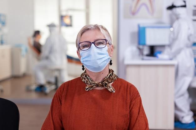 Portret van gepensioneerde patiënt in de tandartspraktijk die op camera kijkt met een gezichtsmasker zittend op een stoel in de wachtkamerkliniek terwijl de arts aan het werk is