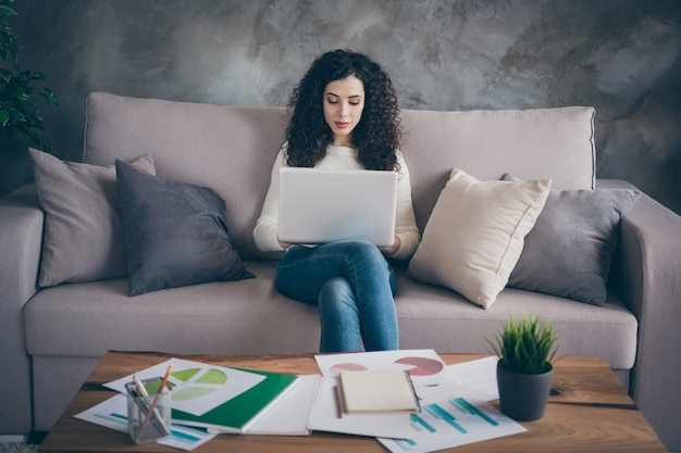 Portret van gericht geconcentreerd meisje zittend op de bank financieel verslag analyse gegevens winst maken op moderne industriële loft interieur stijl woonkamer binnenshuis