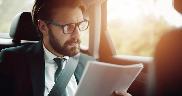Portret van gerichte zakenman zittend op de achterbank in auto documenten te lezen tijdens het reizen