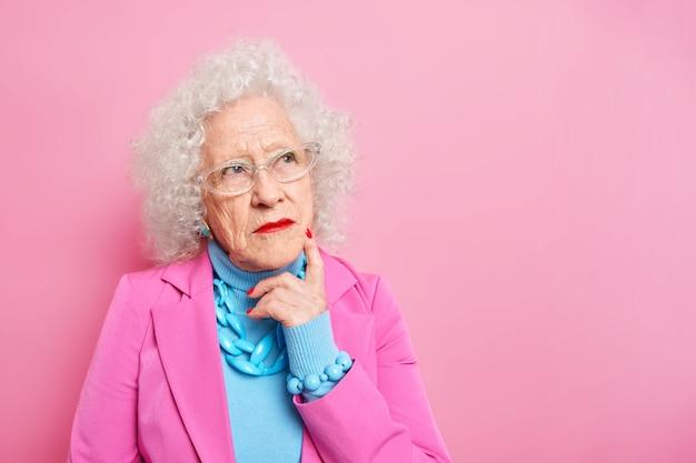 Portret van gerimpelde, doordachte, grijze, oudere dame die opzij is geconcentreerd, herinnert zich dat haar jeugd gekleed in modieuze kleding heldere make-upjurken heeft voor speciale gelegenheden