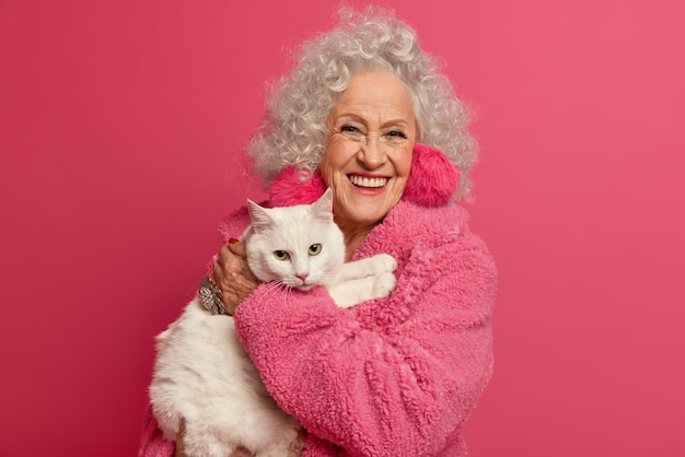 Portret van gerimpelde grootmoeder houdt witte kat op handen, blijft thuis tijdens pandemie-uitbraak, draagt donzige oorbellen, zachte mantel, gaat huisdier voeden, geïsoleerd op roze muur. vrouw met pensioen