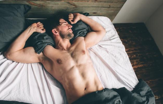Portret van geschikt mannelijk model in slaap in luxueuze slaapkamer gebaad in het heldere warme licht van het ochtendvenster