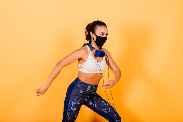 Portret van geschikte afrikaanse vrouw die gezichtsmasker draagt. sportieve vrouw in fitnesskleding staande op een gele achtergrond.