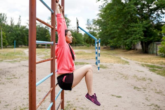 Portret van geschikte en sportieve jonge vrouw die oefeningen, exemplaarruimte doen. gezonde levensstijl