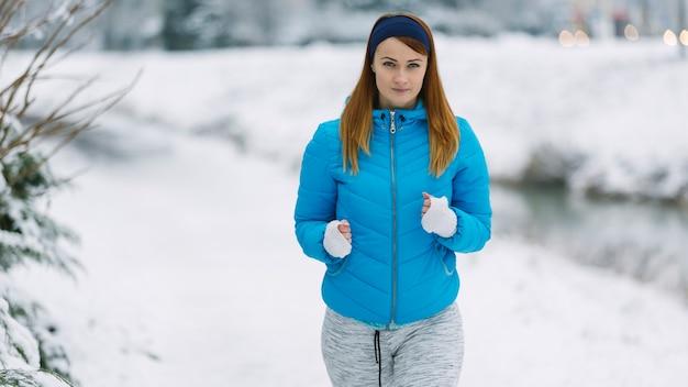 Portret van geschikte jonge vrouw die in de winter loopt