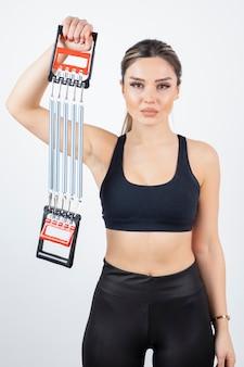 Portret van geschikte vrouw die gymnastiekhulpmiddel toont.
