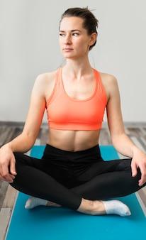 Portret van geschikte vrouw die yoga thuis uitoefenen