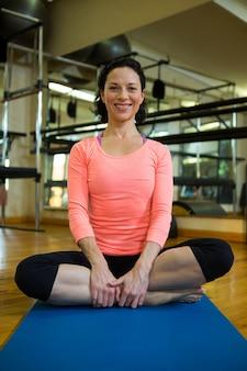 Portret van geschikte vrouw die yoga uitvoert