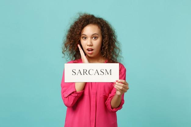 Portret van geschokt afrikaans meisje in roze casual kleding met tekstbord sarcasm geïsoleerd op blauwe turquoise muur achtergrond in studio. mensen oprechte emoties, lifestyle concept. bespotten kopie ruimte.
