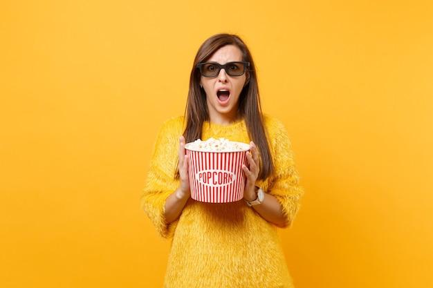 Portret van geschokt bang jong meisje in bonttrui, 3d imax-bril die filmfilm kijkt, met emmer popcorn geïsoleerd op felgele achtergrond. mensen oprechte emoties in de bioscoop, levensstijl.