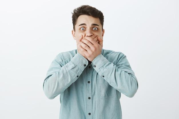 Portret van geschokt bang jonge kerel in vrijetijdskleding