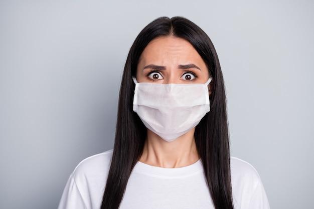 Portret van geschokt doodsbang meisje hoor vreselijke coronavirusepidemie verspreiden nieuws dragen medische masker witte t-shirt geïsoleerd over grijze kleur achtergrond