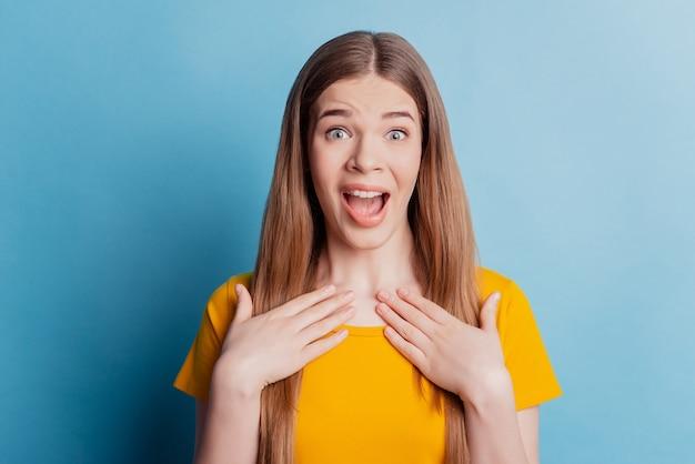 Portret van geschokt funky meisje met open mond palmen borst op blauwe achtergrond
