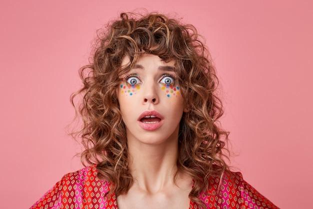 Portret van geschokt jonge krullende vrouw met wijd open ogen en mond, geïsoleerd, gestreepte roze en oranje kleren dragen
