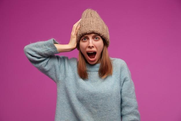 Portret van geschokt, jonge vrouw met donkerbruin lang haar. het dragen van blauwe trui en gebreide muts. haar hoofd aanraken en schreeuwen over paarse muur