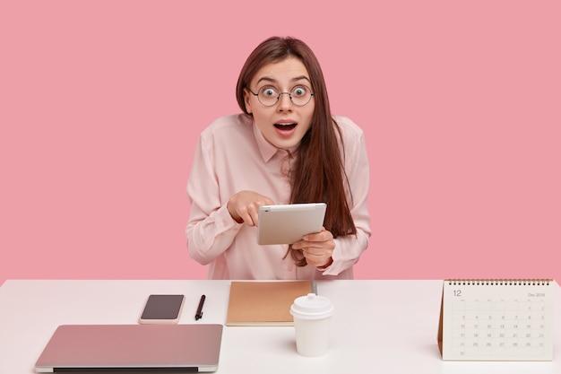 Portret van geschokt jonge vrouw werkt op afstand, houdt touchpad vast, doet onderzoek voor project, houdt mond open
