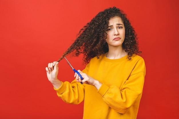 Portret van geschokt krullend meisje dat haar haar met schaar snijdt, dat op rode achtergrond wordt geïsoleerd.