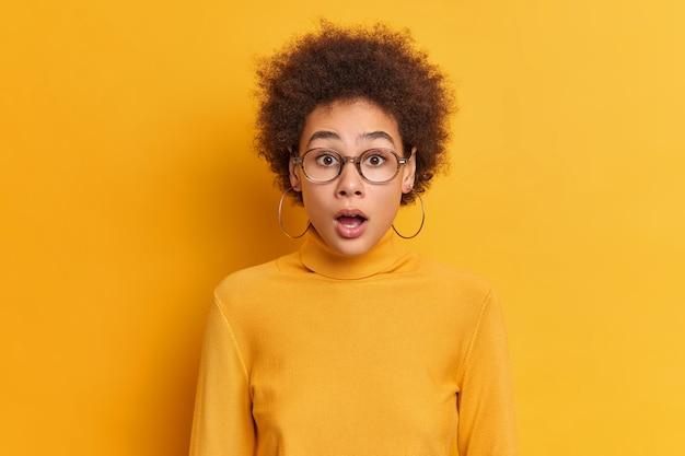 Portret van geschokt krullende vrouw staart met geopende mond reageert op geweldig nieuws draagt doorzichtige bril oorbellen coltrui. sprakeloos onder de indruk afro-amerikaanse tiener houdt de mond open