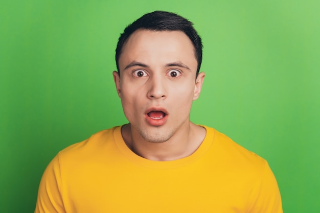Portret van geschokt sprakeloos man open mond verbijsterd gezicht op groene achtergrond